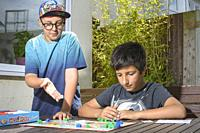 two boys,10-11 years old play monopoly board game,UK.