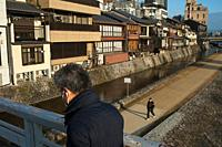 26. 12. 2017, Kyoto, Japan, Asia - A man is seen crossing a bridge over the Kamo River in Kyoto at dawn.