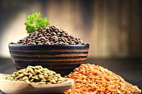 Composition with bowl of lentils on wooden table.