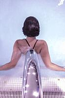 Woman Relaxing in a Hydro Massage Pool with Falling Water on Her Spine in Switzerland.
