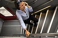 Woman Using Her Smartphone and Walking Up on a Staircase in First Class Train in Switzerland.