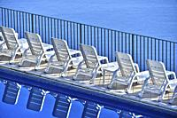 Row of free sunbeds at the swimming pool in a touristic resort.