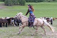 China, Inner Mongolia, Hebei Province, Zhangjiakou, Bashang Grassland, Mongolian horsemen dressed with traditional clothes, lead a troop of horses run...