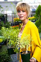 A pretty 42 year old blond woman shopping at a garden store potted euphorbia plants.