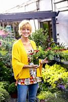 A pretty 42 year old blond woman shopping at a garden store smiling at the camera.