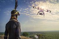 Karo man looking at flying drone. Village of Kolcho, Omo Valley, Ethiopia