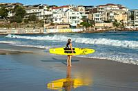 21. 09. 2018, Sydney, New South Wales, Australia - A young female surfer is seen holding her surfboard as she gazes at the open ocean at Bondi Beach.