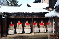 Takayama, Gifu, Japan, Asia - A row of Jizo statues made of stone, wearing red hats and bibs is seen sitting under a wooden shelter at the Hida Kokubu...