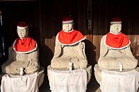 Takayama, Gifu, Japan, Asia - A row of Jizo statues made of stone, wearing red hats and bibs is seen sitting under a wooden shelter at the Hida Kokubu...