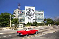 Tourists in a vintage American car in front of the Depiction of Camilo Cienfuegos on the facade of the Communication building at the Plaza de la Revol...