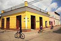 Cyclists in front of the colonial buildings at the street in the historic center, Trinidad, Sancti Spiritus, Cuba, West Indies, Central America
