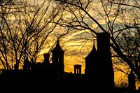 The historic 1855 Smithsonian Institution Administration Building on the National Mall in Washington, DC is silhouetted against a winter sunset and fr...