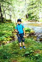 boy child fishing in the river in the mountains in the alps in the summer.