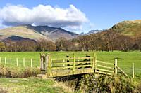 A wooden footbridge over a small beck at Dale Bottom with Blencathra beyond in the English Lake District National Park, Cumbria, England.