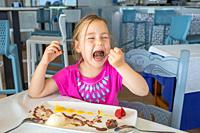 funny cute four years old blonde girl opening big mouth to eat with spoon a delicious sweet dessert: black chocolate, vanilla ice cream, strawberries ...