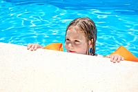 four years old blonde child with orange floater sleeves in arms, armbands, clinging or holding on to the curb of the swimming pool, with blue transpar...