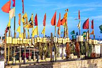Fishing floats and flags set out to dry in the evening sun at Monte Gordo beach, Algarve, Portugal.
