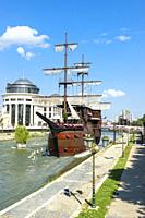 Galleon ship restaurant and bar on Vardar River, Government buildings behind, Skopje, Macedonia.