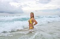 Young woman in a yellow bikkini bathes in the waves in the sea foam on an exotic tropical island. Fuvahmulah Island, Indian Ocean, Maldives, Asia