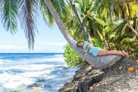 Relaxing woman lies on the coconut palm tree on a tropical beach. Young beautiful woman lying on the palm tree on sea shore. Summer vacation concept i...