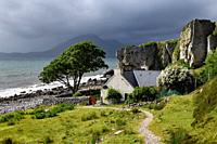 House under cliff at Elgol beach with Red Cuillin Mountains under clouds at Loch Scavaig Scottish Highlands Isle of Skye Scotland UK.