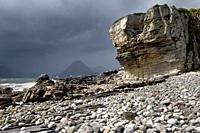Tourist on Elgol beach at Port na Cullaidh with Red Cuillin Mountains under clouds on Loch Scavaig Scottish Highlands Isle of Skye Scotland.