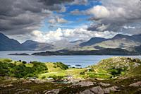 Sun on Ardheslaig village on Loch Beag and fish farm on Loch Shieldaig and Torridon Hills at Upper Loch Torridon Scottish Highlands Scotland.