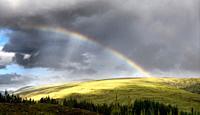 Double rainbow and dark clouds on An Liathanach mountain at Loch a Chroisg near Badavanich Scottish Highlands Scotland UK.