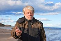 Mature poor man with grey hair at the Baltic sea asks for help in autumn day.