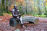 Statue of poet sits on outdoor Robert Burns on bench during autumn at the Birks O'Aberfeldy scenic area in Aberfeldy, Perthshire, Scotland,UK.