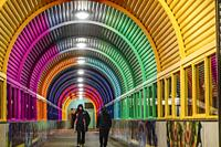 Stockholm, Sweden Pedestrians walk in the covered and colorfully painted passageway at the train station in the Handen suburb south of town.