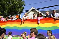People standing on a float with a pride rainbow banner and people walking at the annual Pride March, Windsor, Canada.