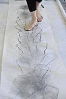 A barefoot woman artist walks on smudged paper during a performance, Windsor, Canada.