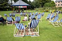 empty deckchairs on the grass in a park at an outdoor summer event in the uk.