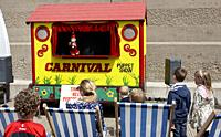 people watching Mr punch from punch and judy puppet show traditional in the uk.