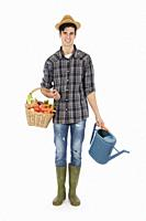 Young farmer with one arm holding a basket with fruit and vegetables, with the other a raincoat, he wears a straw hat, checked shirt and green rubber ...