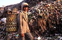 Jakarta, Java, Indonesia, Asia - An Indonesian garbage collector is searching for recyclable materials like plastic and metal at the Bantar Gebang gar...