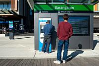 Sydney, New South Wales, Australia - A man is buying a ferry ticket at a ticket machine on Wulugul Walk in Barangaroo South.
