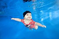 Little boy in a striped suit swim underwater in the swimming poo on a blue water background. Healthy family lifestyle and children water sports activi...