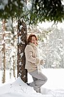Happy red-haired woman having fun on winters day in forest. Latvia.