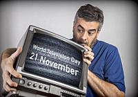 Middle-aged man holds a TV with World Television Day 21 November screen, conceptual image.