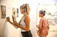 Two female artists hang both representational and abstract works at a Fullerton, CA, art gallery in preparation for an exhibition.