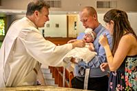 A robed deacon presides at at infant boy's baptism at a Laguna Niguel, CA, Catholic church.