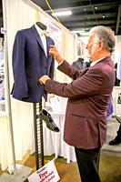 Formally-dressed himself, a formal wear supplier spiffs up a blue tuxedo on exhibit along with a black shoe at a bridal festival in Costa Mesa, CA.