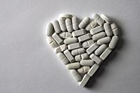 White pills in the shape of heart isolated on white fund, conceptual image.