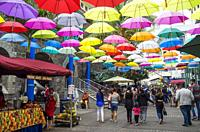 Floating umbrella art display in street at Caudan Waterfront, Port Luis, Mauritius. Caudan Waterfront is a commercial centre in Port Luis, the capital...