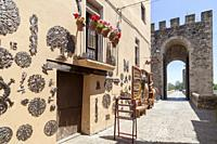 Street view and tower of romanesque bridge and souvenir shop in medieval village of Besalu,Catalonia,Spain.