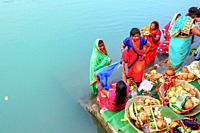 group of women in colourful saris praying in the water of river Ganga at Rishikesh, India.