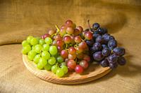Bunches of three colors grapes on wooden dish.