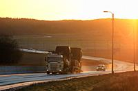 Salo, Finland - November 24, 2018: Scania vehicle carrier hauls new trucks at the warm light of sunset at bypass road on winter afternoon in Finland.
